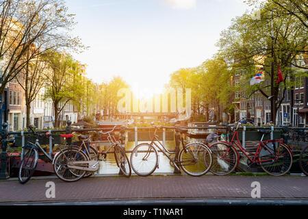 Bicicleta a través del canal de la ciudad de Ámsterdam en los Países Bajos con vistas sobre el río Amstel durante la puesta de sol.