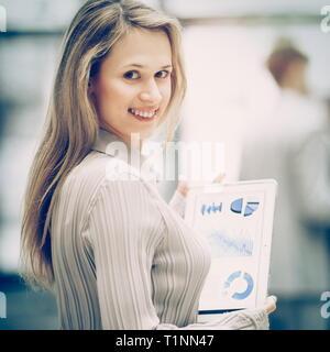 Mujer de negocios de éxito, con un ejercicio gráfico en una tableta en el fondo del equipo empresarial en Office