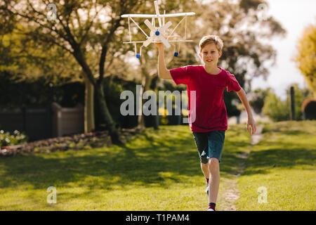Muchacho feliz jugando con un avión de juguete en el parque. Entusiasmado niño corriendo con un avión de juguete al aire libre. Foto de stock