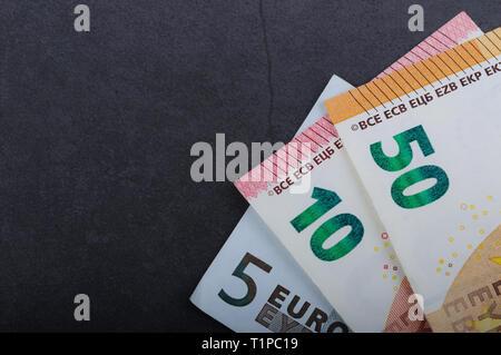 Billetes en euros. Denominaciones diferentes sobre un fondo gris. 5, 10 50 euros Foto de stock