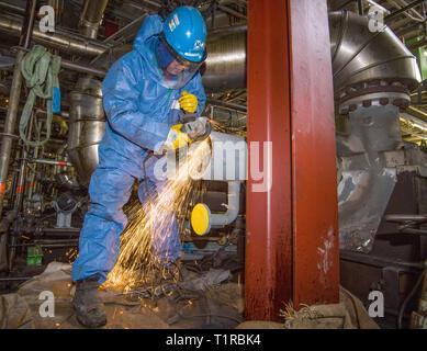 Schwedt, Alemania. 26 Mar, 2019. Un trabajador utiliza una rueda de corte para rectificar un tubo en la zona de destilación de crudo de PCK Raffinerie GmbH. En el PCK refinería de petróleo 24 de las 36 plantas serán inspeccionados hasta la Pascua. Durante la revisión de mantenimiento regular estas se encuentran en un punto muerto. 3.700 empleados de empresas externas vacía, limpiar y lavar los tubos y equipos. A continuación, las posibles anomalías tales como grietas son buscados. 115 grúas están ensambladas. TÜV inspectores inspeccionar los sistemas al final. Crédito: Patrick Pleul/dpa-Zentralbild/ZB/dpa/Alamy Live News