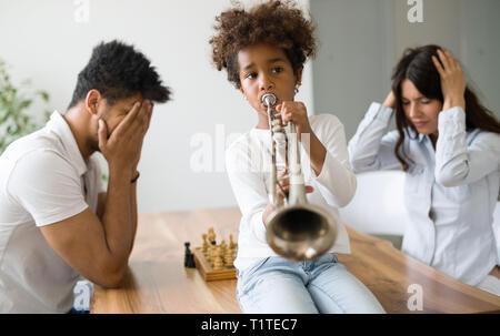 La madre y el padre tratando de jugar al ajedrez, mientras su hijo juega trompeta