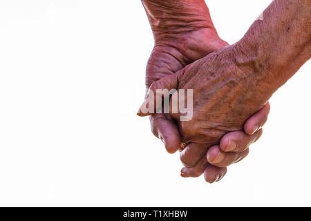 Captura recortada de la pareja de ancianos tomados de la mano exterior con fondo blanco. Se centran en las manos