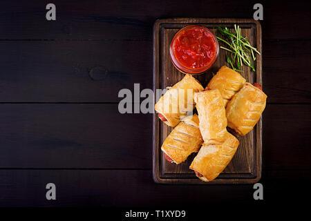 Salchichas en la masa sobre una placa de madera con salsa de tomate. Vista superior