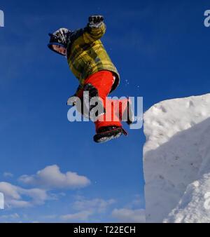 Un joven (6 años) saltando desde la cima de un acantilado de nieve