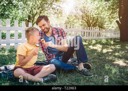 Bonita imagen de dos muchachos sentados sobre una manta en el parque. Tienen helados en las manos. El hombre está dando a su hijo para probar sus helados. Niño es abrir la boca Foto de stock