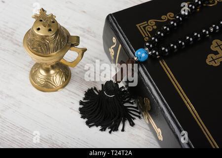 Acercamiento de la Santa Biblia, rosario con la cruz y el incensario sobre fondo de madera blanca. Concepto de la religión y la fe.