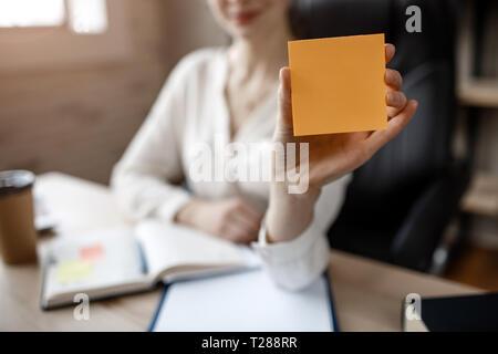 Hermosa joven empresaria hold pegatinas de color amarillo en la mano. Ella les muestran a la cámara. Modelo sentarse en la habitación. La luz del día.