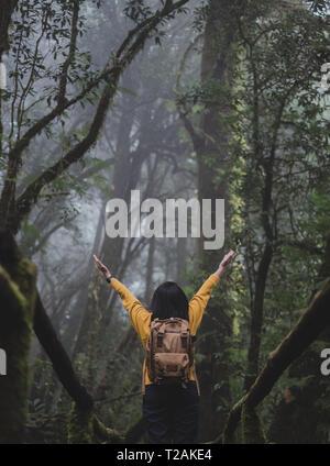Mujer Asiática backpacker brazos arriba en foerest en senderos naturales,Vacaciones en rain forest