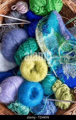 Bolas de lana de colores en una canasta de tejer