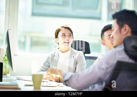 Tres jóvenes empresarios asiáticos reunidos en oficina, feliz y sonriente.