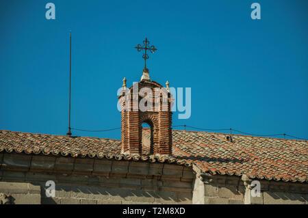 Pequeño arco de ladrillo de la azotea con una cruz de hierro forjado sobre top en Avila. Con una imponente muralla alrededor del centro de la ciudad de estilo gótico en España. Foto de stock