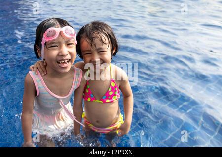Poco asiáticos hermanas chinos jugando en la Piscina Piscina