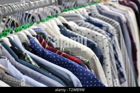 Elegante de camisas en perchas en la tienda borrosa. En vísperas del Viernes Negro. Antecedentes para el diseño de una tienda por departamentos.