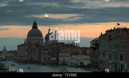 La luna llena se eleva sobre la basílica de Santa María en Venecia, Italia