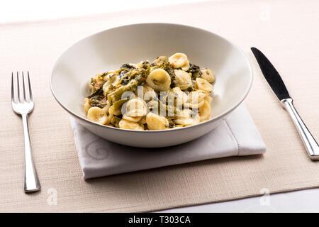 Orecchiette con cime di Rapa, o un plato de pasta orecchiette con brócoli rabe, un plato regional de la región de Puglia, Italia sirve en un plato en la mesa