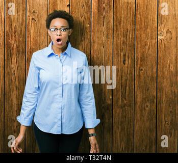 Hermosa joven mujer de negocios americano africano sobre antecedentes aislados miedo y conmovido con expresión de sorpresa, miedo y entusiasmado cara.