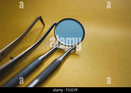 Instrumentos dentales de cerca sobre un fondo amarillo. La prevención de las enfermedades bucodentales.