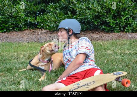 Un pit bull ama adolescentes tirando de su propietario en su monopatín por la calle. Lo hacen una vez o dos y, a continuación, jugar en el césped para descansar. Foto de stock