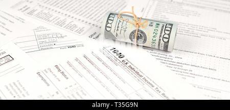 1040 Formulario de devolución de impuestos sobre la renta de las personas físicas con el rollo de billetes de dólar americano cerca. Concepto de período fiscal en Estados Unidos