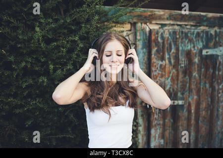 Mujer joven en una camiseta blanca sonriente con los ojos cerrados y escuchar música a través de auriculares al aire libre, campo.
