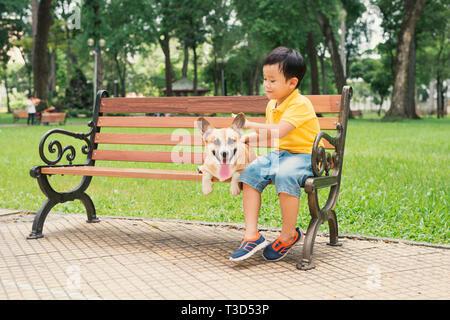 Los niños y perros al aire libre. Niñito asiática disfrutando y jugando en el parque con su adorable Pembroke Welsh Corgi.