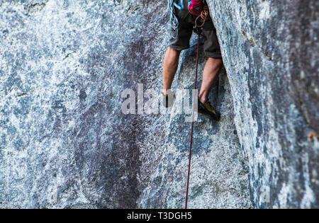 Un hombre escalador ejecuta (subiendo un largo camino sin proteger la posible caída) en el pequeño fume Bluffs área de escalada, Squamish, BC.