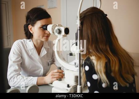 Atractivo femenino médico oftalmólogo es controlar la visión del ojo de la mujer joven en la moderna Clínica. El médico y el paciente en oftalmología clínica.