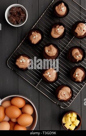 Pasteles de hadas sobre una bandeja de refrigeración con ingredientes, sobre un fondo de madera gris angustiado, tomada desde arriba Foto de stock
