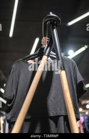 Vestidos negros colgando en el stand de la tienda de ropa iluminada