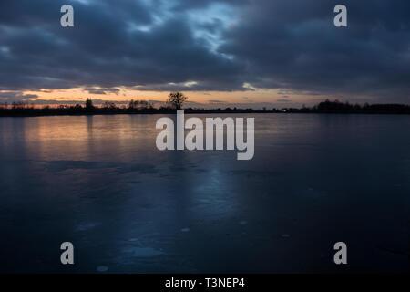 Cielo nublado después del atardecer desde el lago congelado y reflejar la luz en el hielo - noche vista de invierno Foto de stock