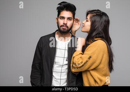 Hermosa mujer india susurrando a novios oído sobre fondo gris Foto de stock
