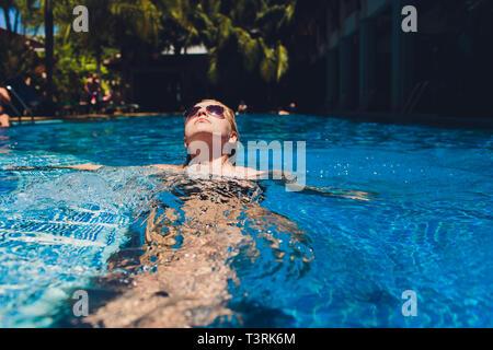 Hermosa mujer de relax en el agua de la piscina. Chica con piel bronceada sana, hermosa cara, y el pelo mojado disfrutando de sol del verano en los calurosos días de verano en