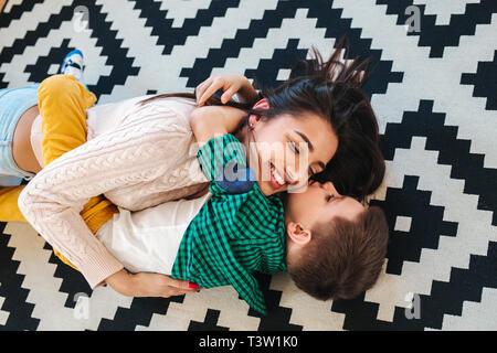 Vista superior de la hermosa mujer y su pequeño hijo lindo sonriente mientras yacían en el suelo