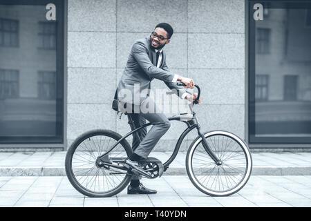 Empresario montando bicicleta al trabajo por la mañana