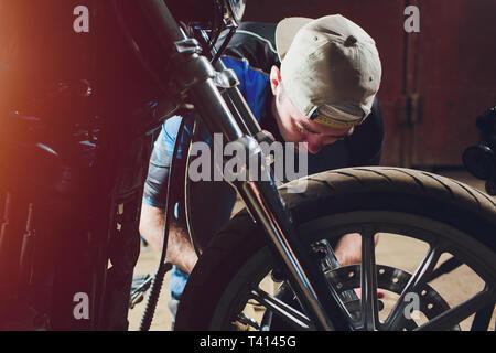 El hombre la fijación de bicicleta. Seguro joven reparación de moto cerca de su garaje.
