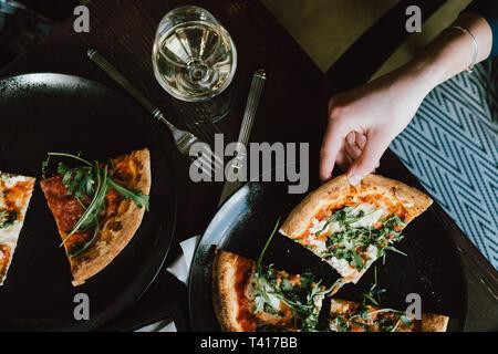 Mujer sentada en una mesa comiendo pizza
