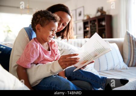 Cerca de la joven madre sentada en un sofá en el salón leyendo un libro con su niño pequeño que está sentado sobre su rodilla, vista lateral Foto de stock