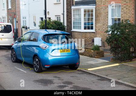Renault Zoe coche eléctrico vehículo con baterías cargadas con un cable eléctrico de una casa interna. En el Reino Unido. (106) Foto de stock