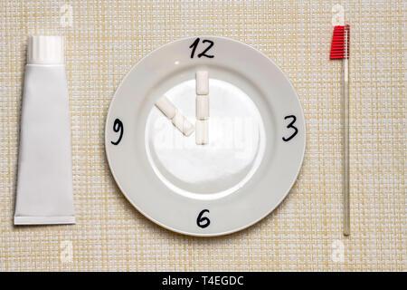 Limpieza de los dientes de la rotura. Tiempo para el cepillado de dientes durante el trabajo o comer. Símbolo de reloj en la placa. Proteger los dientes de caries dental o placa conce
