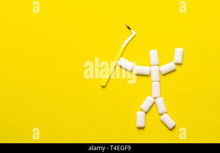 Concepto de limpieza de dientes con espacio de copia. Almohadillas de goma de mascar en la forma de un pequeño hombre con un cepillo para la limpieza de llaves. Proteger los dientes de esmalte del diente