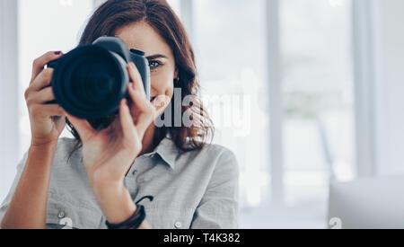 Mujer fotógrafo tomando fotos con su cámara DSLR profesional en interiores. Toma de fotografía femenina en la cámara digital.