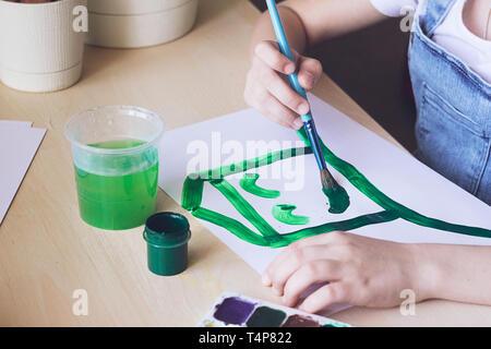 El niño pinta una casa verde brillante con una sonrisa. Concepto de la ecología . Asignación escolar o la creatividad.