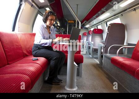 Mujer de negocios sentada en el tren de primera clase, trabajando con un ordenador portátil y un teléfono móvil, Suiza