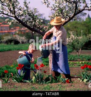 Mi abuelo y su pequeña hija regar las flores en el jardín