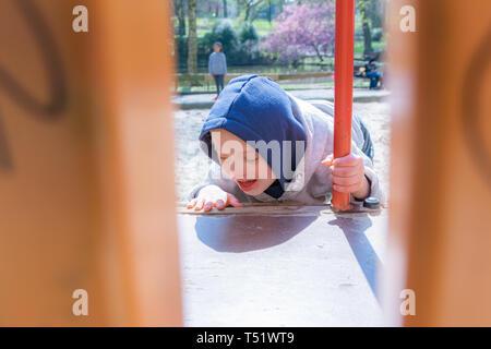 Defecto,guarderías,medicina y personas concepto: Rubio chico con Síndrome de Down jugando en un parque.
