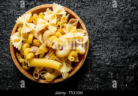 Diferentes tipos de pasta seca en un recipiente. Negro sobre fondo rústico