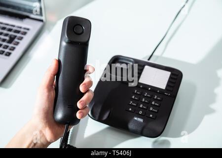 Close-up de la mano de una empresaria marcando el número de teléfono para hacer llamadas telefónicas de oficina