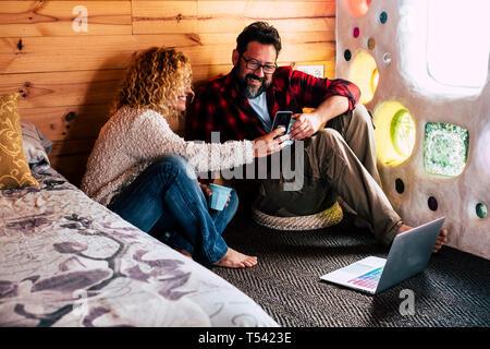 Pareja de Adultos disfrutando de la tecnología en el hogar o el hotel viaja con mirar la pantalla de un dispositivo de telefonía móvil y utilizando un ordenador portátil conectado a internet en el flo
