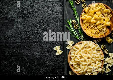 Diferentes tipos de pasta cruda en cuencos con el romero. Negro sobre fondo rústico